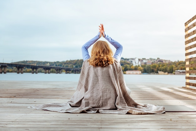 マインドフルネスアウェイ。川の近くで瞑想をしている格子縞で覆われた女性