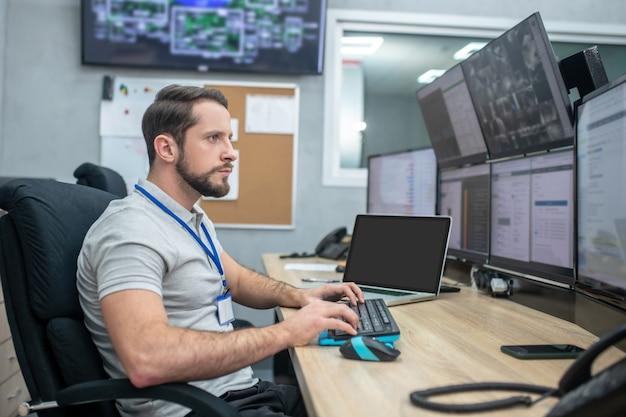Внимательность. серьезный молодой бородатый мужчина сидит на рабочем месте, глядя на экраны компьютеров, его руки над клавиатурой