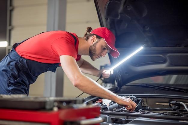 マインドフルネス。ワークショップで車のオープンフードの近くにランプを手に作業服を着た若い大人の自動車整備士