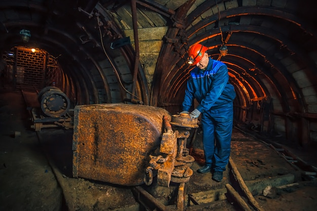 A miner in a coal mine stands near a trolley. copy space. miner repairing a trolley