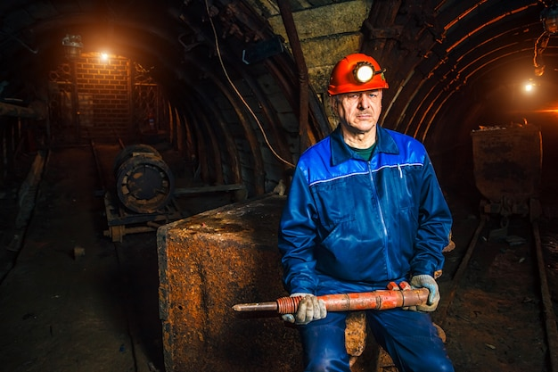Miner with a jackhammer sitting on a trolley in a coal mine