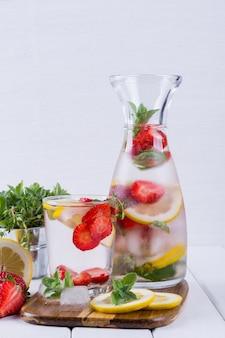 딸기, 얼음, 허브 및 민트 잎 미네랄 워터 주입, 흰색 표면에 수제 해독 소다수 제조법.