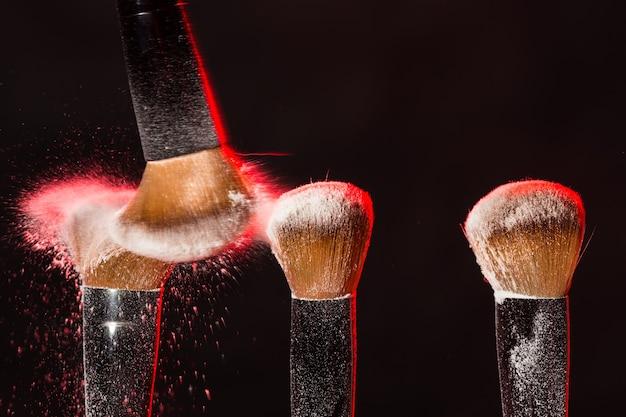 Минеральная кисть для макияжа и косметики, смахивающая красную пудру с другой поверх черной