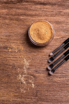 Mineral powder foundation with brushes on a wooden background. eco-friendly and organic beauty products