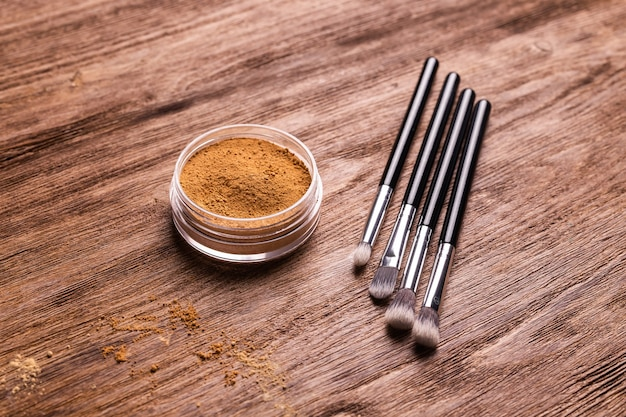 Mineral powder foundation with brushes on a wooden background ecofriendly and organic beauty