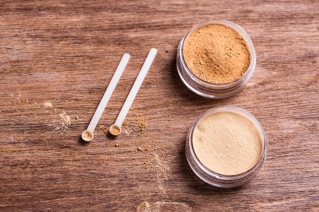 Минеральная пудра разных цветов с дозатором ложки для макияжа на деревянном фоне