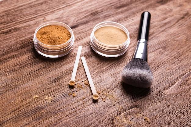 Минеральная пудра разных цветов с дозатором ложки для макияжа на деревянной поверхности