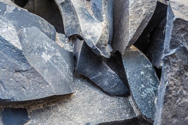 山に積み上げられた大量のシュンガイトの鉱物学。シュンガイトの石。