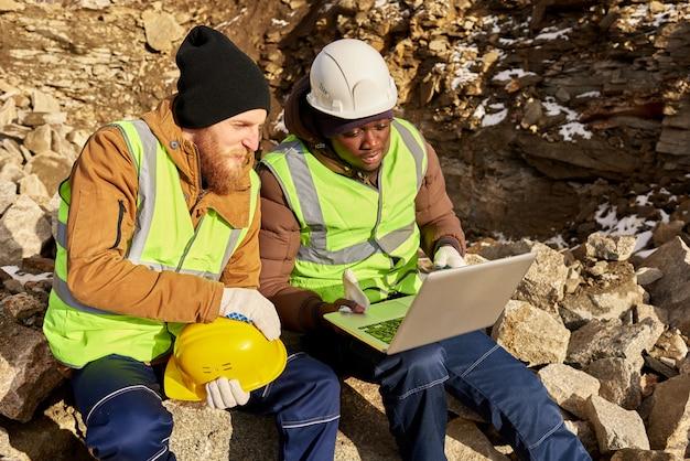 発掘現場でコンピューターを使用する鉱山労働者