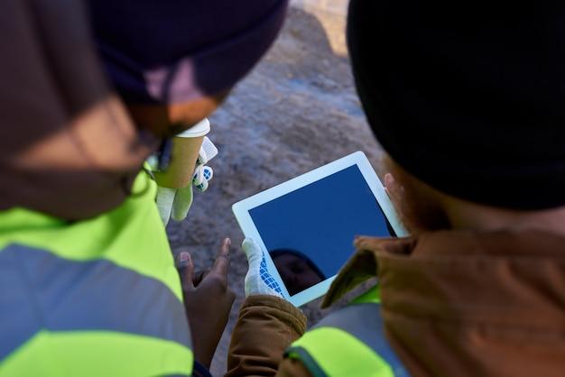 屋外でタブレットを使用する鉱山労働者