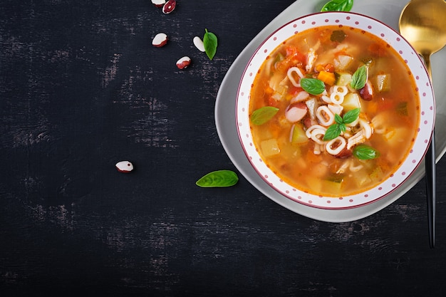 Минестроне, итальянский овощной суп с пастой на темном столе. вид сверху, плоская планировка, копия пространства