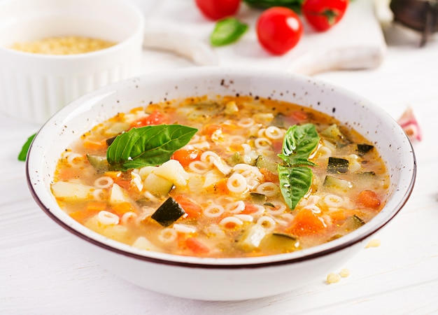 Minestrone, italian vegetable soup with pasta on white table.