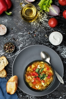 Minestrone soup in a black dish on a dark table