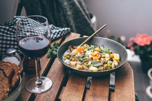 레드 와인 한 잔과 함께 나무 테이블에 미네스트로네 수프