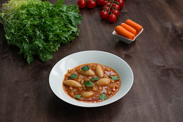 Minestrone soup with pasta and herbs. italian cuisine. dark wooden background