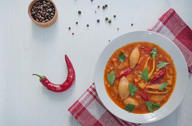 Minestrone soup with pasta and herbs. italian cuisine. white wood background