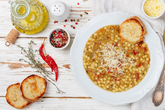 Minestrone thick soup with vegetables , pasta, lentils, cheese and spices,