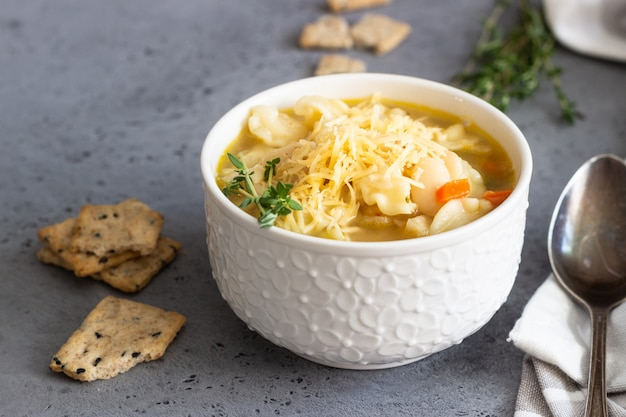 Minestrone with pasta and white beans topped with thyme and served with crackers
