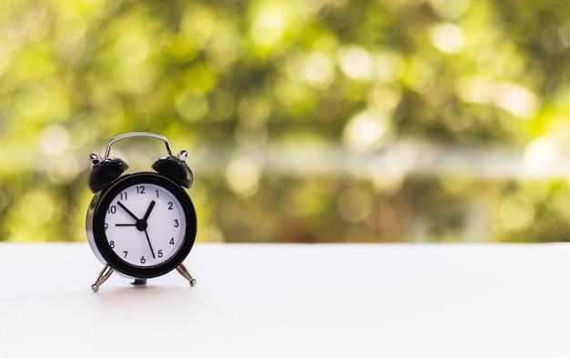 Mini alarm clock against natural blurred green background