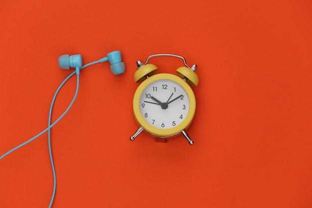 오렌지 배경에 미니 알람 시계와 이어폰.