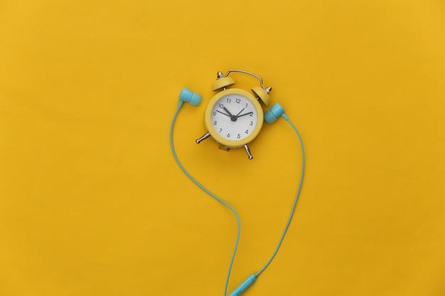 노란색 배경에 미니 알람 시계와 이어폰.
