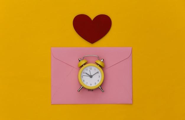 ミニ目覚まし時計と封筒、黄色の背景にハート。幸せなバレンタインデー。