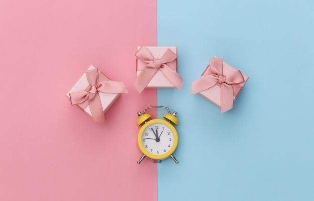ピンクブルーのパステルカラーの背景にミニ目覚まし時計とギフトボックス。