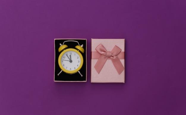 紫の背景にミニ目覚まし時計とギフトボックス。