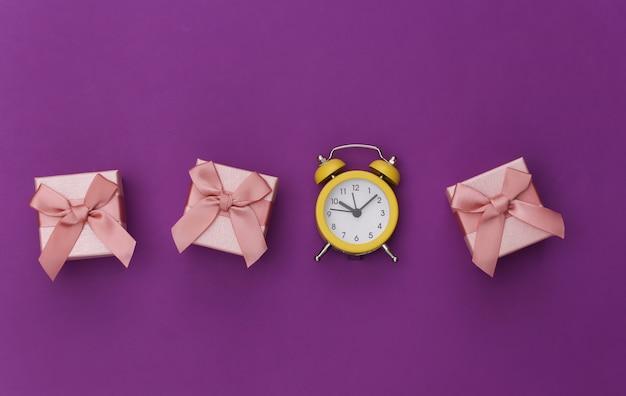 紫色の背景にミニ目覚まし時計とギフトボックス。