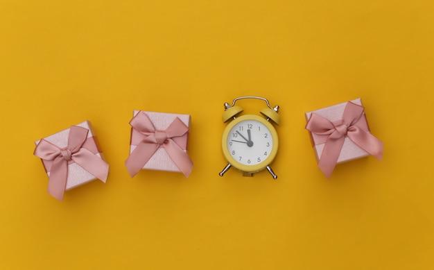 黄色の背景にミニ目覚まし時計とギフトボックス。