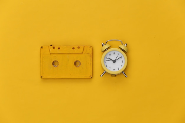노란색 배경에 미니 알람 시계와 복고풍 오디오 카세트.