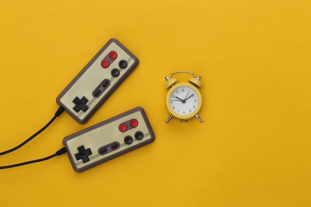 黄色の背景にミニ目覚まし時計とレトロなジョイスティック。