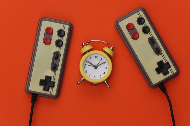 オレンジ色の背景にミニ目覚まし時計とレトロなジョイスティック。