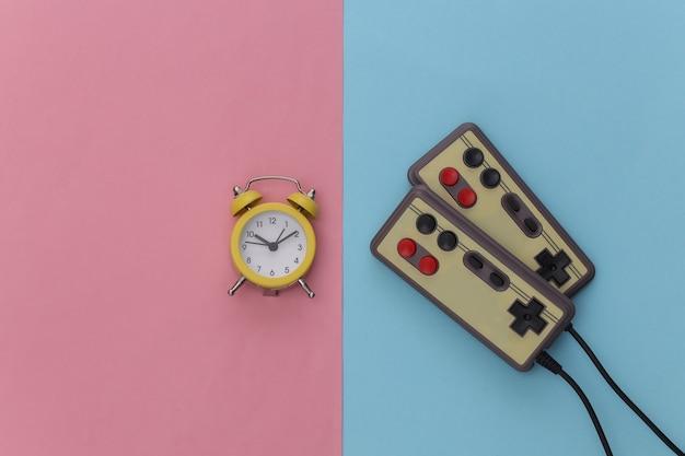 ピンクブルーのパステルカラーの背景にミニ目覚まし時計とレトロなジョイスティック。