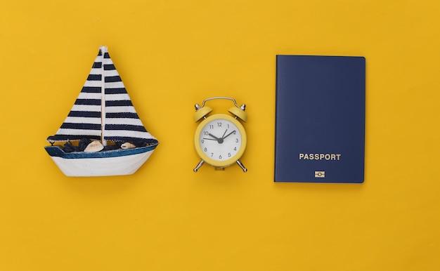 미니 알람 시계와 배, 노란색 배경에 여권. 여행할 시간입니다.