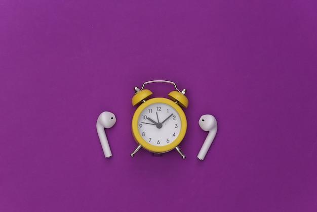 보라색 배경에 미니 알람 시계와 무선 헤드폰.