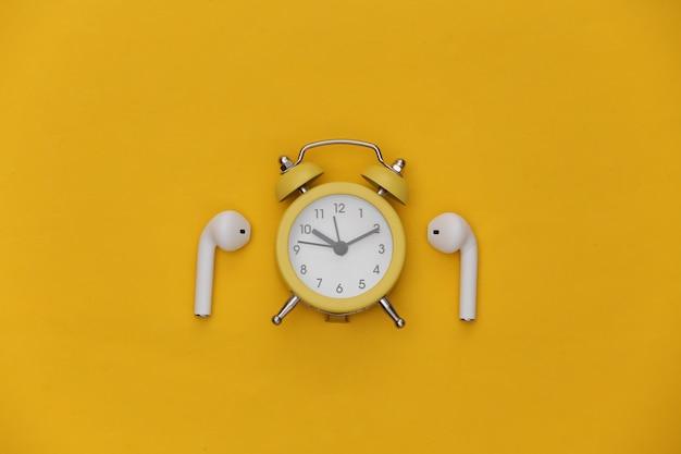 노란색 배경에 미니 알람 시계와 무선 헤드폰.