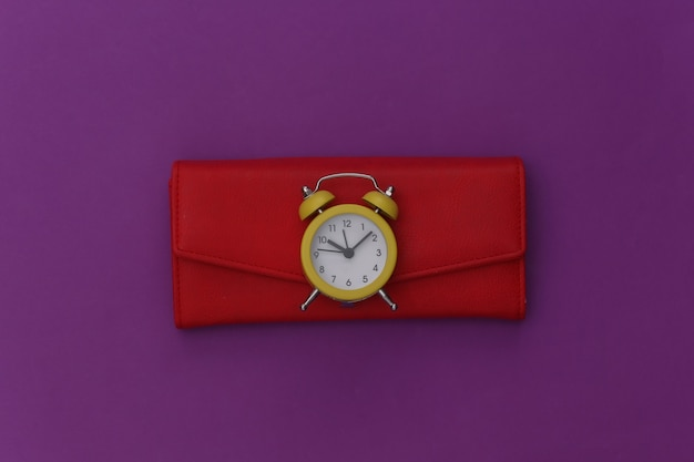 Mini alarm clock and red wallet on purple background.