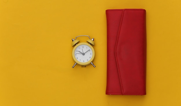 Mini alarm clock and red wallet on yellow background.