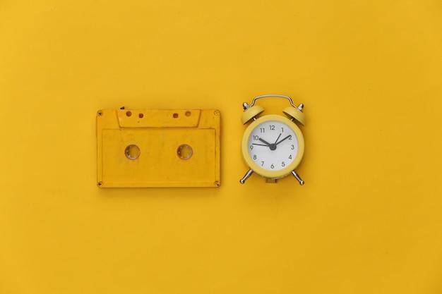 Mini alarm clock and retro audio cassette on a yellow background.