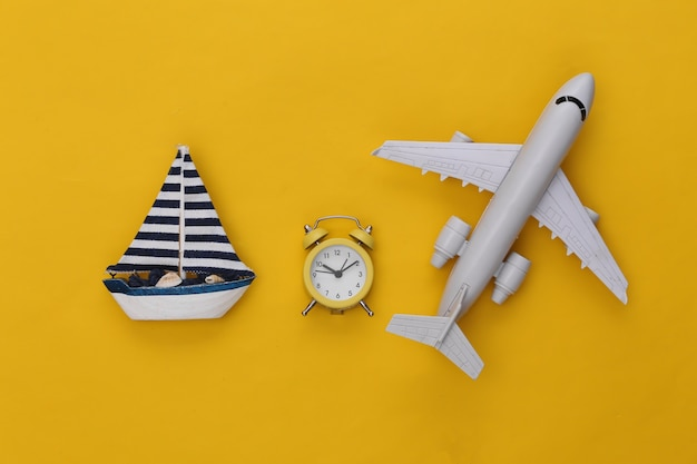 Mini alarm clock and ship, air plane on a yellow background. time to travel.
