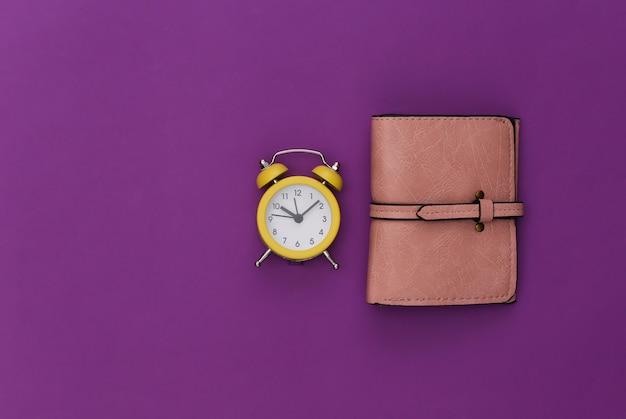 Mini alarm clock and wallet on purple background.