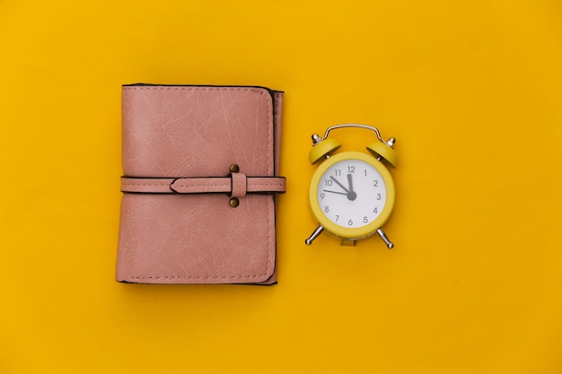 Mini alarm clock and wallet on yellow background.