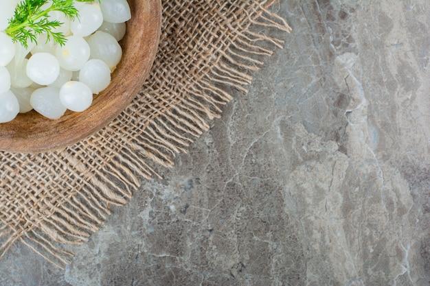 Mini cipolline in una ciotola su tovagliolo di iuta su marmo.