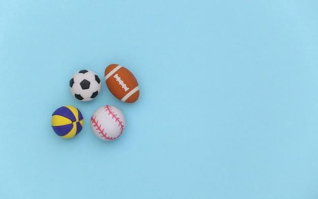 파란색 배경에 다른 스포츠의 미니 공. 미니멀리즘 스포츠 개념입니다. 평면도. 플랫 레이. 공간을 복사합니다.