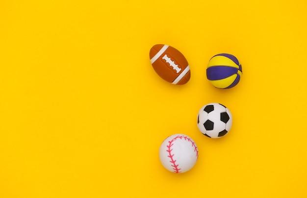 노란색 배경에 다른 스포츠의 미니 공입니다. 미니멀리즘 스포츠 개념입니다. 평면도. 플랫 레이. 공간을 복사합니다.