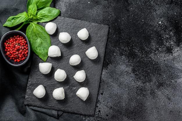 Мини шарики из сыра моцарелла, ингредиенты для салата капрезе. черный фон. вид сверху. копировать пространство