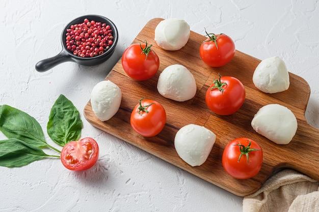 Мини-шарики из сыра моцарелла, на деревянной доске ингредиенты для салата капрезе