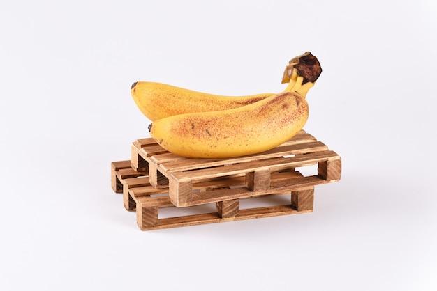 Мини-бананы на транспортировке деревянных поддонов на белом фоне.