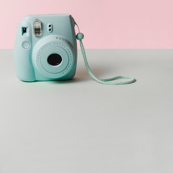 Mini blue instant camera on gray desk against pink background